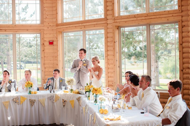 bride and groom smiling and clapping at head table